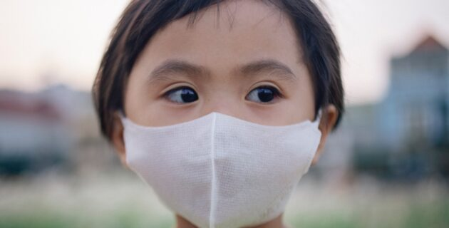 Young child wears a face mask outside