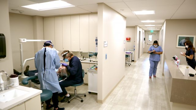Masked clinic workers provide dental services to a patient