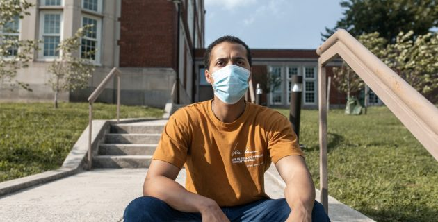 A young Black man wearing a face mask sits on steps outside a brick building