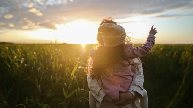 A child gets a piggyback ride in front of a sunset