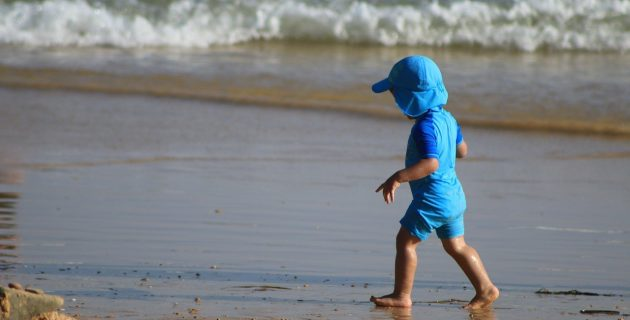 A child in a sun hat walks along the beach on a hot day