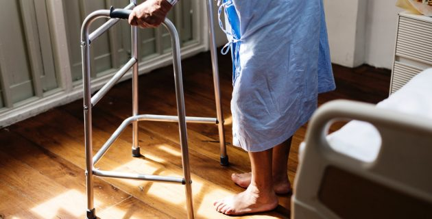 A man in a hospital gown stands with a walker