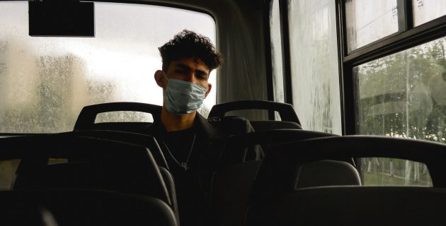 Man in a facemask sits on a bus while it pours outside
