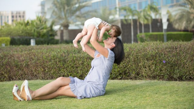 A woman lifts a baby while sitting in the grass.