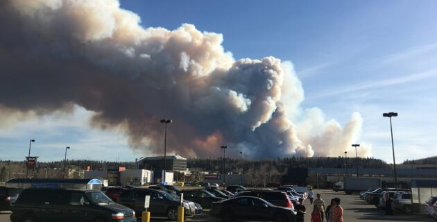 The Fort McMurray fire burns behind a parking lot with cars and children