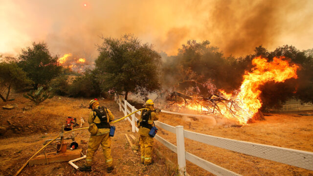 Firefighters from Stockton, Calif. put out flames off of Hidden Valley Rd. while fighting a wildfire