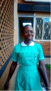 Photograph of Ms. Kevin Nalubwama standing in a in a turquoise dress outside of a building