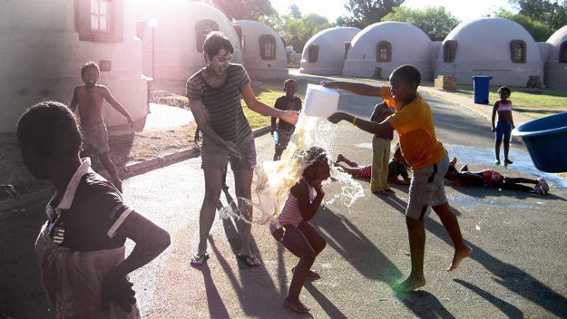 Kathleen Wirth and children celebrating the first day of spring with a friendly water fight at an orphanage for children infected or affected by HIV/AIDS in Johannesburg, South Africa.