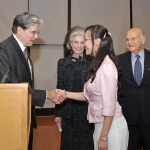Dean Frenk shakes hands with Volunteer Leadership Award scholar Wen Xie as Deeda Blair and Maurice Tempelsman look on.