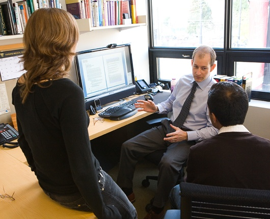 Image of Stephen Resch Speaking to Colleagues in CHDS Office.