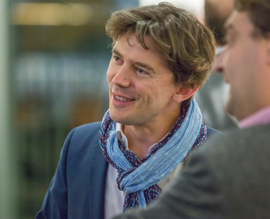 Stephane Verguet smiling at talking with others at event.