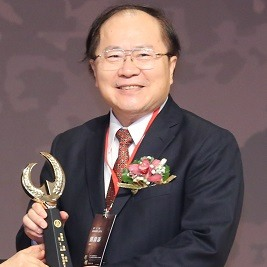 Jin Tan Liu holding an award and smiling at camera