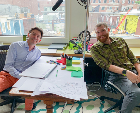 Stephane Verguet and Jake Waxman smile for the camera while storyboarding