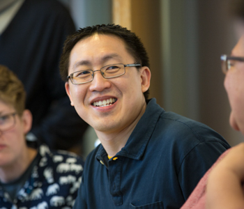 Stephen Sy smiling offcamera seated at meeting