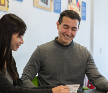 Mike Eber and Lily Hsieh looking down at work on desk smiling