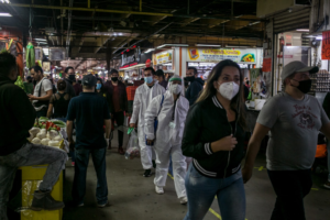Busy marketplace with people wearing PPE
