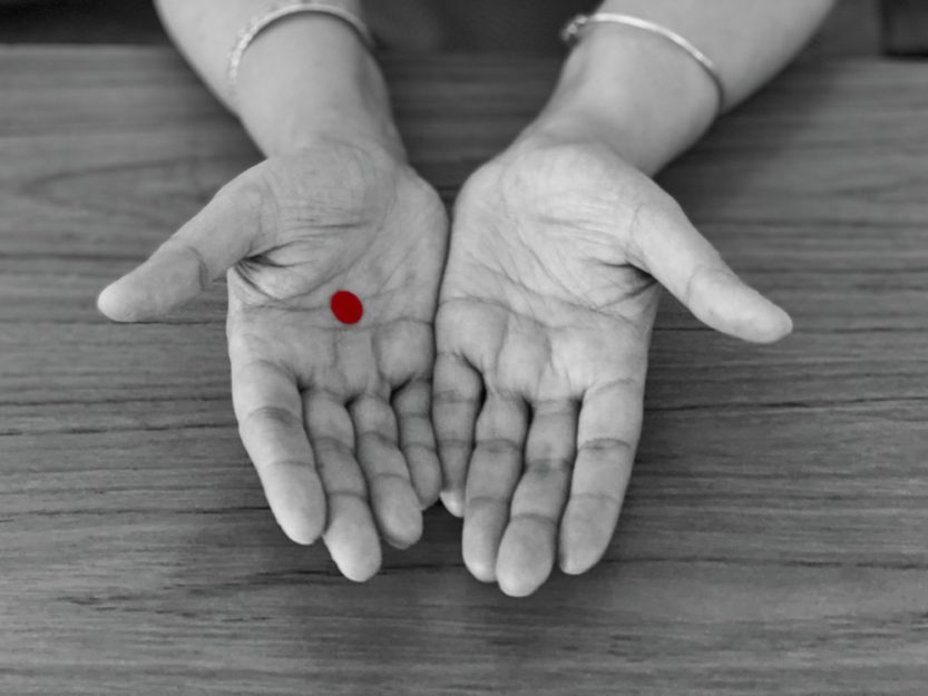 Photo of outstretched hands, one with a red dot