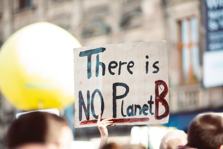 "Image of person holding sign that reads, ""There is no Planet B"""