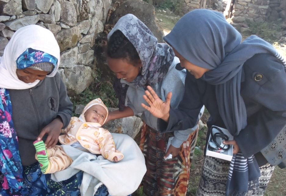 Three women with smiling baby in Ethiopia