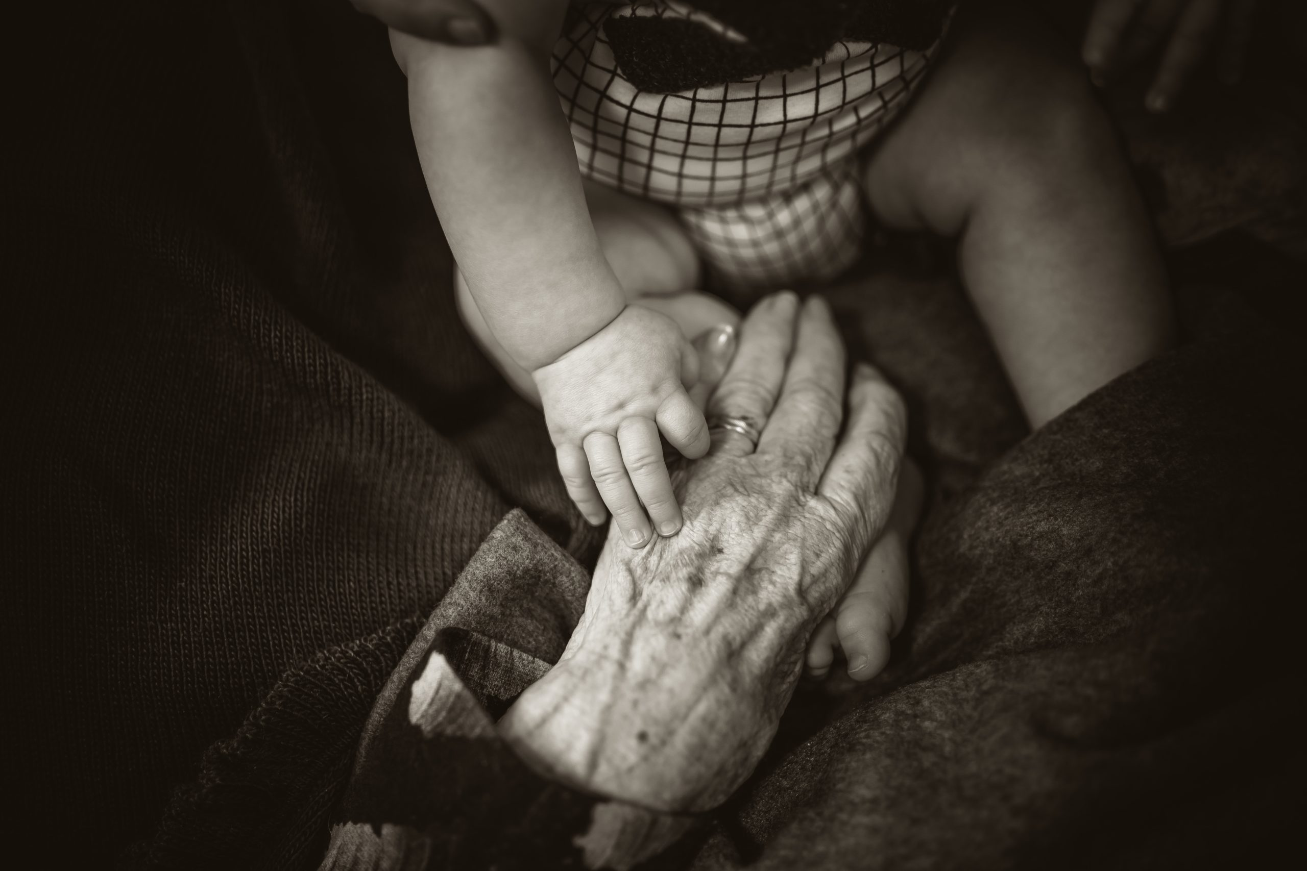 Photo of elderly person holding a baby's hand