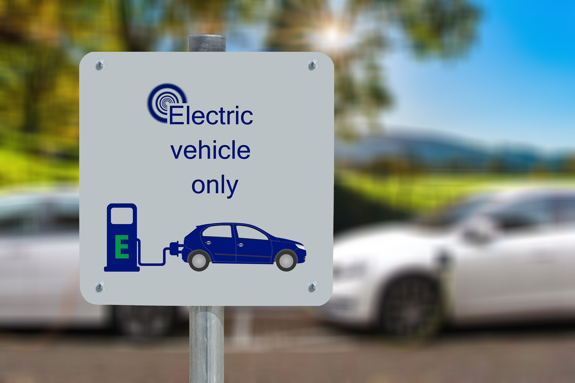 """a sign saying """"electric vehicle charging only"""" with two cars in the background and a sunny landscape with green grass and trees"""