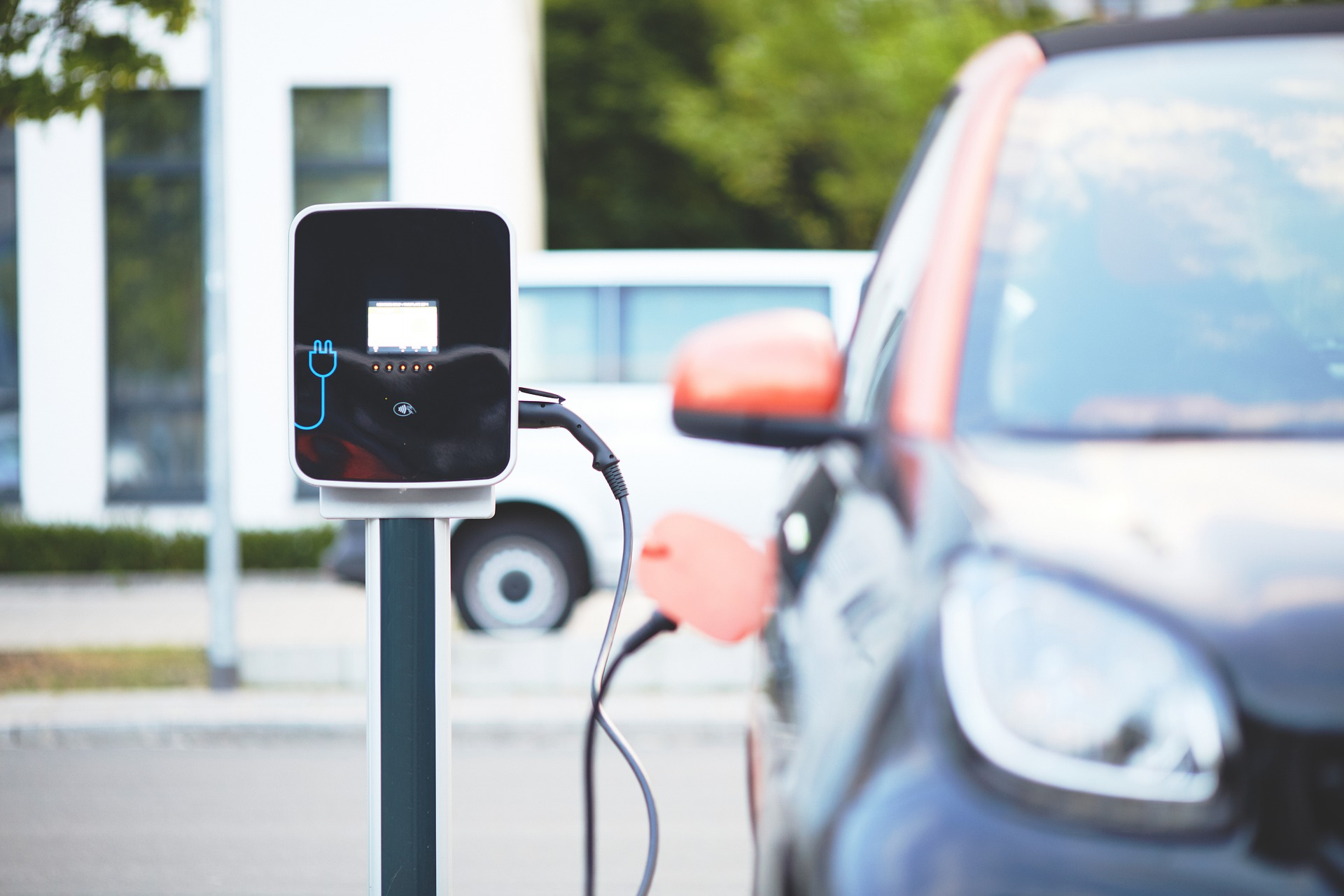 photo of a black and orange electric car plugged into a black charging point with a blue plug icon