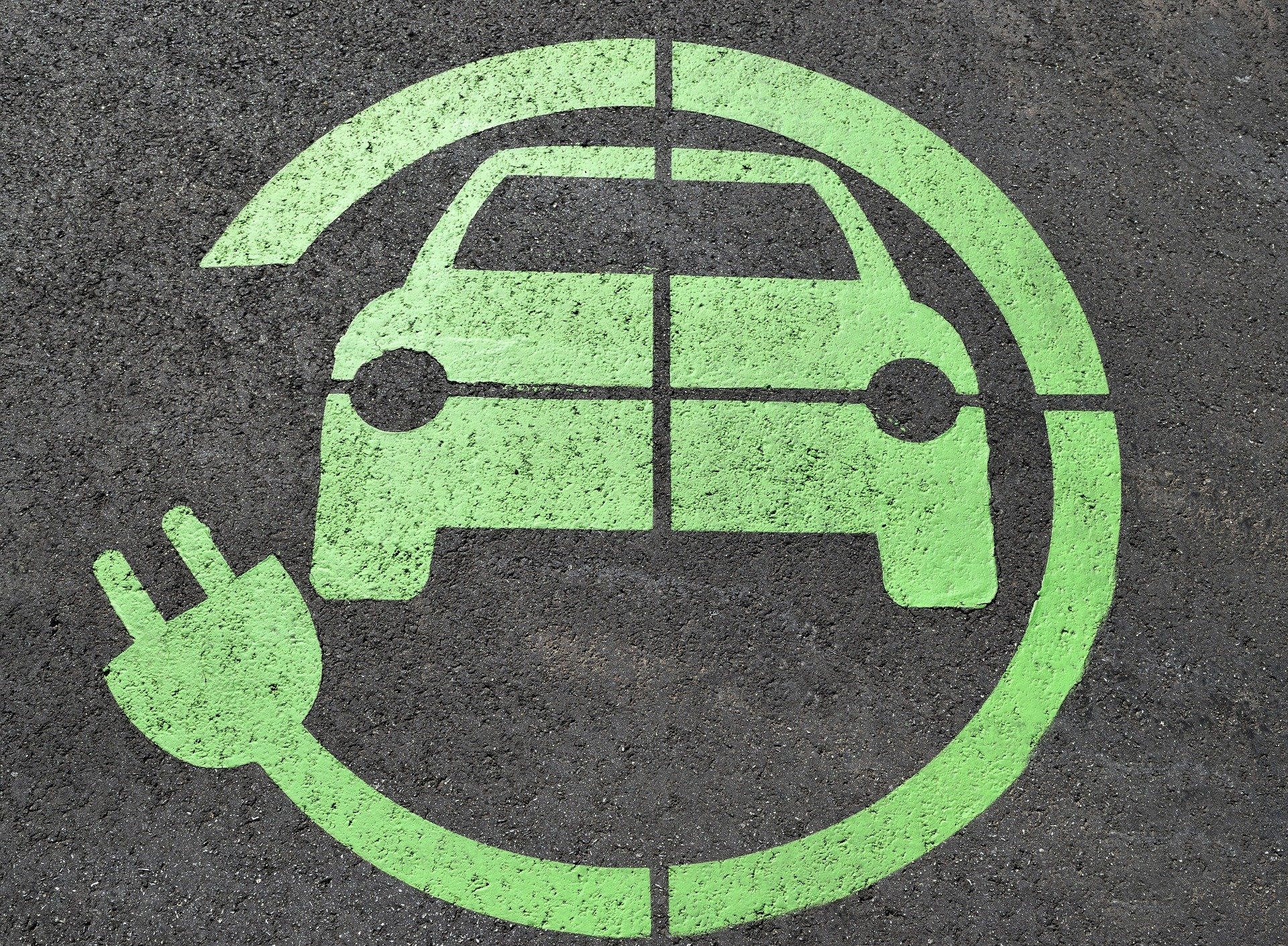 green painting on asphalt of a car with electric plug around it signifying electric vehicle parking