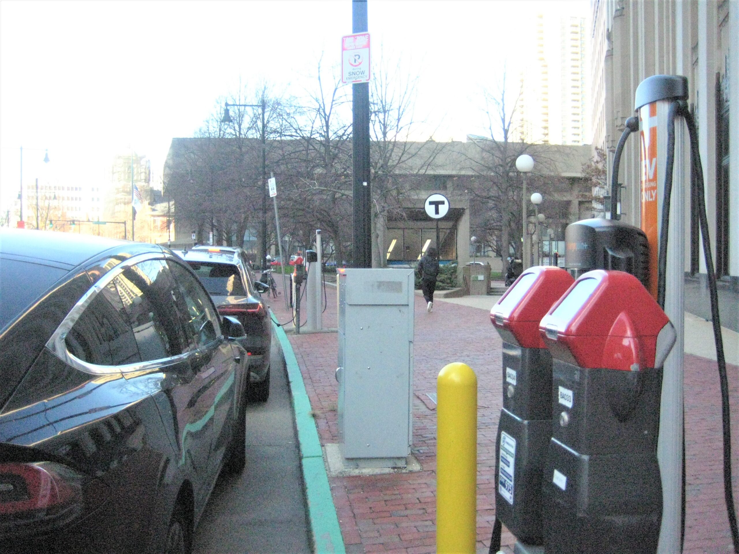 parallel parked electric vehicles charging at charging stations on the side of the road