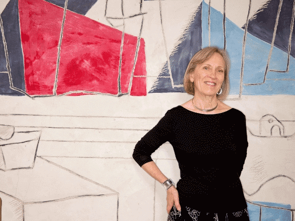 Claudia Goldin standing in front of Abstract Art