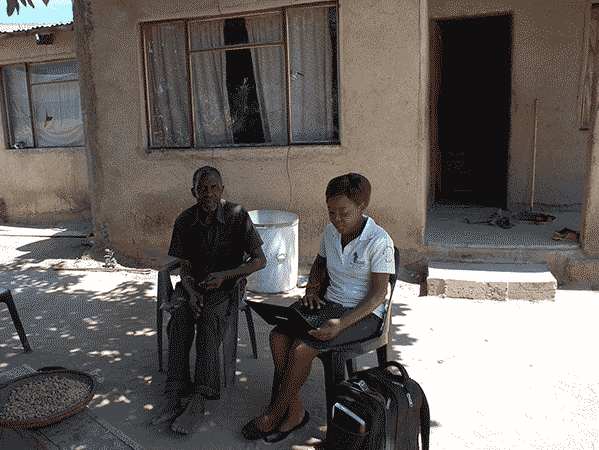 An older South African man and a healthcare worker do an intake sitting outside in rural South Africa