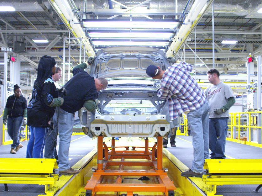Assembly workers work on a Chrysler car at a Michigan plant.