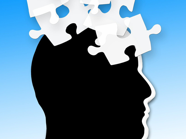 Illustration of profile of a person's head with puzzle pieces