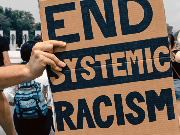 """Handwritten sign """"End Systemic Racism"""""""