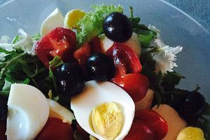Hardboiled eggs on a salad of tomatoes, greens, and olives