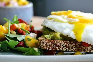 Poached egg with runny yolk on mashed avocado and whole grain bread, with a side salad of arugula and mango red pepper salsa