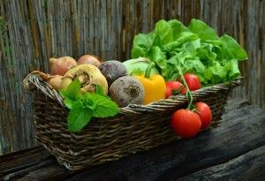 basket of vegetables including tomatoes bell peppers onions lettuce mint