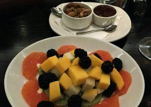 A platter of oranges, mangoes, blackberries, and kiwi, with nuts and chocolate