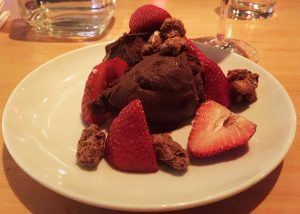 a scoop of dark chocolate ice cream with strawberries and almonds