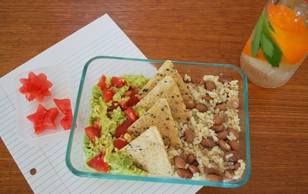 Mexican-themed lunch with guacamole, brown rice, beans, watermelon, and flavored water