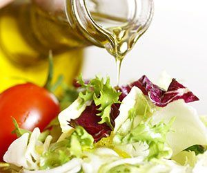 Olive oil being poured onto salad with tomatoes