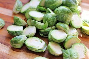 Brussels sprouts cut in half lying on a wooden cutting board