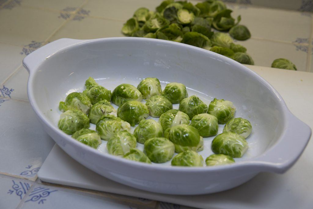 Brussels sprouts coated in olive oil in a roasting dish