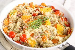 A bowl of quinoa with tomatoes and herbs