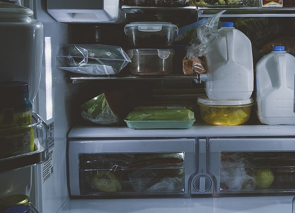 Full refrigerator with bottles of milk, and containers of food