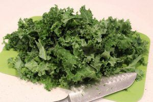 kale and a knife on a cutting board