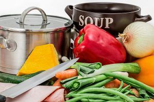 various vegetables next to two cooking pots