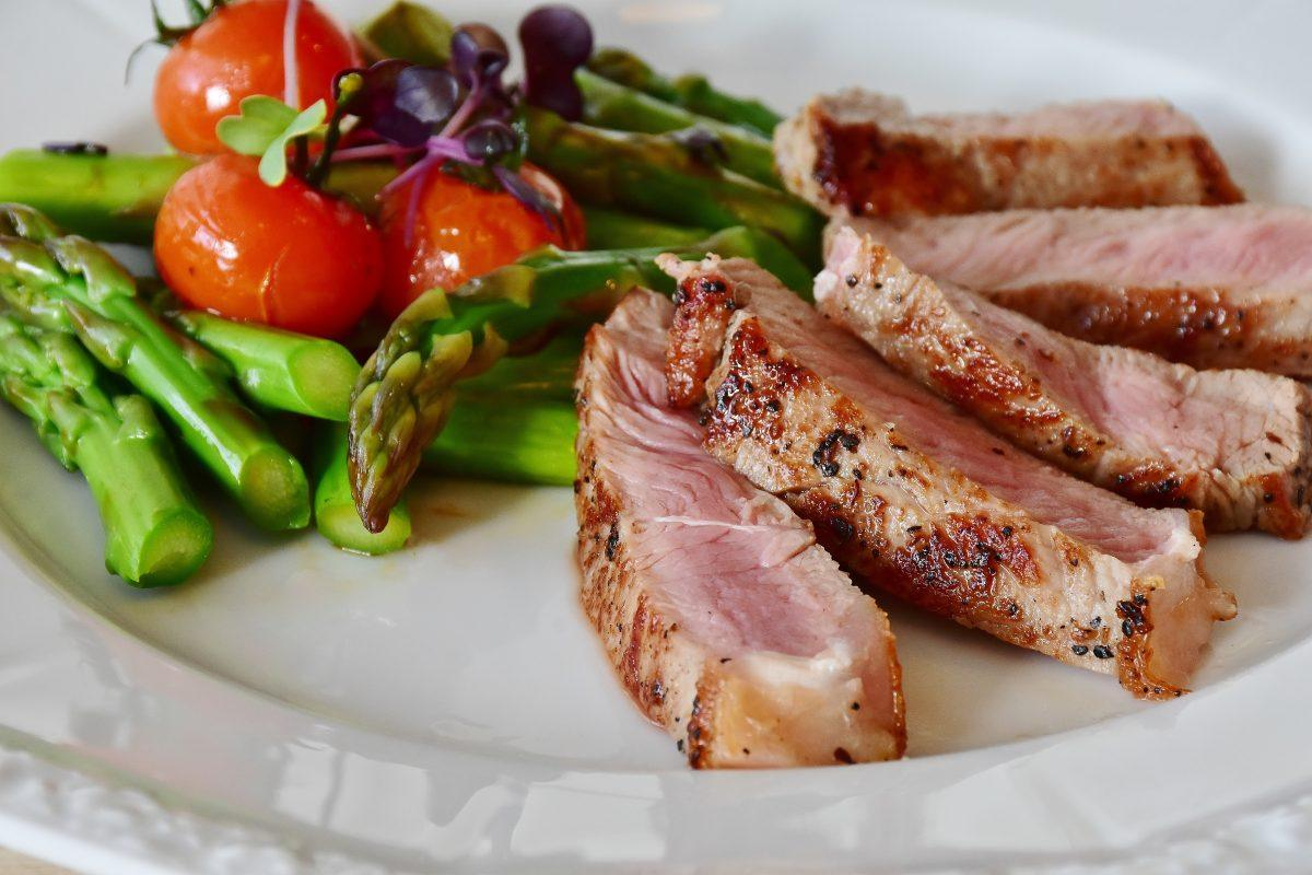 rare meat with asparagus, tomatoes, and microgreens