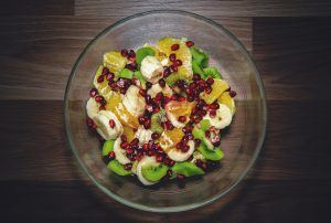 sliced bananas in a fruit salad with kiwi, oranges, and pomegranates
