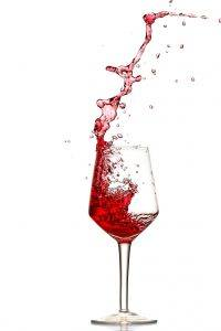 Red wine splashing out of glass
