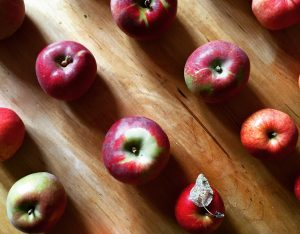 Red and green apples laying on a wooden table